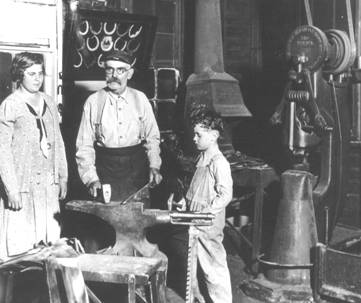 William Siebler inside his blacksmith shop with  youngest daughter, Mildred, and youngest son, Lee.   Aurora, Nebraska.  Circa 1932
