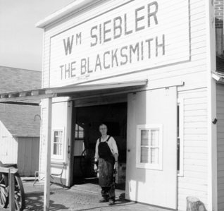 Ron Siebler stands in front of his Great Grandfather's blacksmith shop.